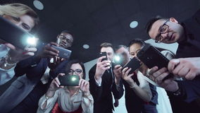 A group of journalists photographed using their smartphones. A group of people in suit of different nationalities take photos using their smartphone and stock video footage