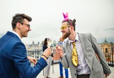 A group of joyful businesspeople having a party outdoors on roof terrace in city. A large group of joyful businesspeople having a party outdoors on roof terrace royalty free stock image