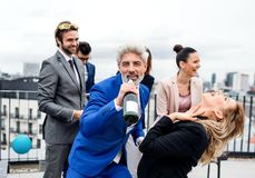 A group of joyful businesspeople having a party outdoors on roof terrace in city. A large group of joyful businesspeople having a party outdoors on roof terrace stock images