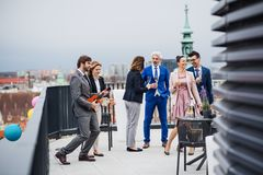 A group of joyful businesspeople having a party outdoors on roof terrace in city. A large group of joyful businesspeople having a party outdoors on roof terrace royalty free stock photo