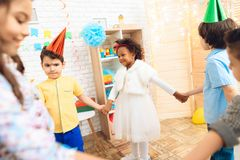 Group of joyful children dancing round dance on birthday party. Concept of children`s holiday. Happy children have fun on celebration Royalty Free Stock Images