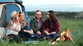 Group of joyful man and woman sitting near bonfire together. Shot on RED Raven 4k Cinema Camera