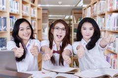 Group of joyful schoolgirls show thumbs up Stock Image