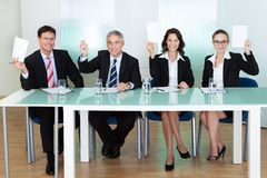 Group of judges holding up blank cards. Group of four stylish professional judges seated at a long table holding up blank cards for their scores Stock Photos