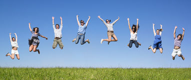Group jumping. Group of friends Jumping in meadow under blue sky Stock Photos