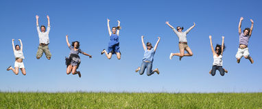 Group jumping. Group of friends Jumping in meadow under blue sky Stock Images