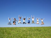 Group jumping. Group of friends Jumping in meadow under blue sky Royalty Free Stock Photo