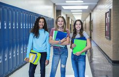 Group of Junior High school Students standing together in a school hallway. Female classmates smiling and having fun together during a break at school stock photo