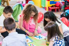 Group of kids applying colorful plasticine during educational activity. Group of kids applying colorful plasticine on various drawings printed on paper sheets stock images