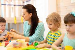 Group of kids on art classes with teacher in kindergarten stock photos