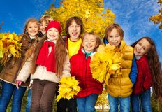 Group kids in autumn park. Group of seven kids around 10 years old , boys and girls, standing together in the park with autumn yellow maple tree on background Stock Photos