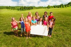 Group of kids with blank baner. Group of children holding blank banner showing blank placard board to write it on your own text, standing on the grass field on Stock Photography