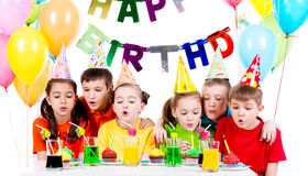 Group of kids blowing candles at the birthday party. Stock Photo