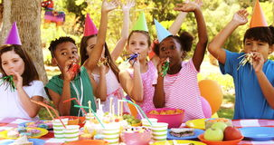 Group of kids blowing party horn while celebrating a birthday. In park 4k stock video