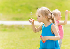 Group of kids blowing soap bubbles outdoors Stock Photos