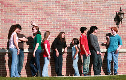Group of kids by brick wall. Diverse group of multi-ethnic teens talking outside Stock Photo