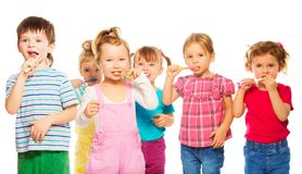 Group of kids  brushing their teeth. Three happy little 3-4 years old kids group standing with toothpaste Stock Photography