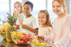 Group of kids at the buffet of elementary school. Multicultural group of children at the primary school buffet take fruits royalty free stock photography