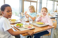 Group of kids in the canteen of the elementary school. Having lunch royalty free stock photo