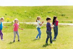 Group of kids catching soap bubbles outdoors Stock Image