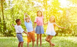 Group of kids cheering and dancing in summer. Interracial group of kids cheering and dancing in summer in the park Stock Photo