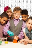 Group of kids on chemistry lesson. Group of diversity kids boys and girls conductive experiments with periodic table on background Stock Photos