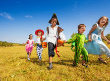 Group of kids with costumes running in park Stock Photography
