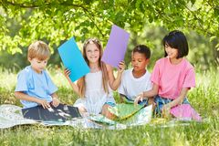 Group of kids in creative crafting. Multicultural group of children in creative tinkering in the summer in the park Stock Photography