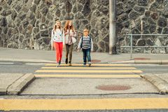 Group of 3 kids crossing the road, walking back to school royalty free stock image