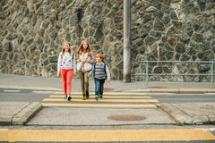 Group of 3 kids crossing the road, walking back to school stock photo
