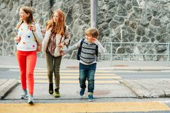 Group of 3 kids crossing the road, walking back to school stock images