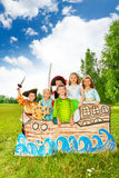 Group of kids in different costumes stand on ship. Group of kids in different costumes stand on the ship made of cardboard and performing play together and smile Royalty Free Stock Photos