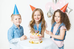 Group of kids in festive cap sit near birthday cake and smile. Celebration. Birthday party. Balloons on the background Royalty Free Stock Image