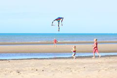 Group of kids flying kite on the beach Stock Photo
