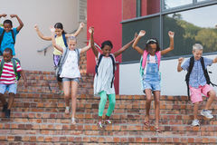 Group of kids getting down from staircase Stock Images