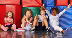 Group of kids in gym holding thumbs up. Happy group of kids in preschool gym holding their thumbs up royalty free stock photos