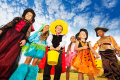 Group of kids in Halloween costumes looks down Royalty Free Stock Photos