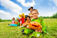 Group of kids in Halloween costumes sitting. Group of kids in Halloween costumes sit in long row on the grass with boy holding a pumpkin Royalty Free Stock Image