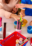 Group of kids hands painting picture on desk . Royalty Free Stock Images