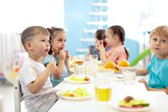 Kids have a lunch in daycare centre. Children eating healthy food in kindergarten stock photography