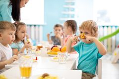Group of kids have lunch in daycare. Child boy dabbles at the table royalty free stock image