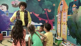 Group of kids having fun in entertainment center. Happy children smiling while listening an animator. Entertainment on kids Birthday party stock video