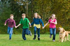 Group of kids having fun running. A group of four kids and a dog holding hands and running Royalty Free Stock Photo