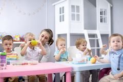 Babies eating healthy lunch in nursery or daycare centre royalty free stock images