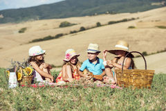 A group of 4 kids having a picnic day. 4 cute kids wearing hats having fun on a picnic Royalty Free Stock Images