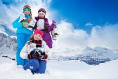 Group of kids with ice skates. Three happy smiling Caucasian girls friends standing outside with ice-skates with mountain on background for copy space Royalty Free Stock Image