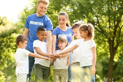 Group of kids joining hands with volunteers stock photography
