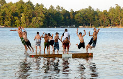 Group of kids jump into Lake. A group of eleven kids ages 11-13 jumping off on a dock into a lake at sumer camp royalty free stock images