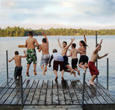 Group of kids jumping into Lake. A group of eight kids ages 11-13 jumping off on a dock into a lake at summer camp royalty free stock image