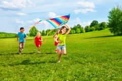 Group of kids with kite. Four little kids running in the park with kite happy and smiling Royalty Free Stock Image